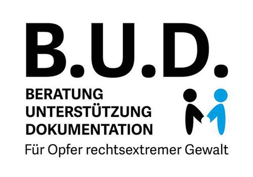"""Logo von B.U.D. e.V., dem Trägerverein der Beratungsstelle B.U.D. In schwarzen Buchstaben steht dort """"B.U.D. Beratung. Unterstützung. Dokumentation. Für Opfer rechtsextremer Gewalt."""" Neben dem Schriftzug sind zwei Figuren abgebildet, die einander gegenüberstehen und sich an den Händen halten. Eine Figur ist schwarz, die andere blau."""